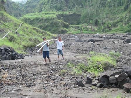 ANGKUT PIPA RUSAK—Dua orang warga Desa Klakah, Selo mengangkut pipa rusak yang diterjang banjir lahar dingin di Kali Apu, Selasa (11/1).  (FOTO: Espos/Ahmad Mufid Aryono)