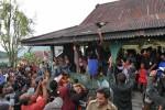 KEJAR AYAM -- Warga berebut mencoba menangkap ayam yang dilemparkan ke atas atap sebagai bagian tradisi Mondosiyo di Desa Pancot, Tawangmangu, Karanganyar, Selasa (21/2/2012). (JIBI/SOLOPOS/Farid Syafrodhi)