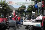 AJAK MOGOK -- Sejumlah peserta aksi berupaya mengajak para buruh di pabrik PT Konimex di Cemani, Grogol, Sukoharjo untuk keluar dan bergabung, Selasa (1/5/2012). Namun karena pintu pabrik tetap tertutup, tak ada buruh di dalam yang menanggapi ajakan unjuk rasa itu. (JIBI/SOLOPOS/Iskandar)