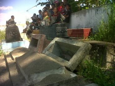 DIBONGKAR-Warga menyaksikan batu nisan yang dirusak oleh orang tak bertanggung jawab di Permakaman Dukuh Bangilan,