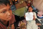 Seorang ibu korban kebakaranm perkampungan di Tambora, Jakarta Barat menunjukkan surat undangan pemungutan suara di pondok daruratnya, Rabu (19/9/2012). Jumlah pemilih pada Pilkada putaran kedua menjadi sebanyak 6.996.951 orang sementara pada putaran pertama 11 Juli lalu jumlah pemilih sebanyak 6.962.348 orang. (JIBI/SOLOPOS/Antara)