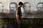 Seorang warga melintas di dekat mural yang ditempel di dinding jembatan DUkuh Atas, Jakarta, Rabu (19/9/2012). Mural tersebut berisi pesan perdamain bagi kedua calon gubernur yang akan bertarung pada putaran ke 2 Pilkada DKI Jakarta, Kamis (20/9/2012). (JIBI/SOLOPOS/Antara)