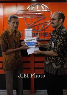Kepala PT Pos Indonesia Cabang Solo, Achmad Chairul Hadi (kanan) menyerahkan hadiah secara simbolis kepada Isbandi di kantor pos tersebut, Jumat (21/9/2012). (Agoes Rudianto/JIBI/SOLOPOS)