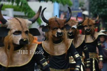 Warga mengenakan kostum sapi saat mengikuti Kirab Hajat Ageng Jagalan di Jagalan, Solo, Minggu (30/12/2012). Gunungan yang terdiri dari kerupuk kulit turut dikirab keliling kampung sebelum diperebutkan warga. (JIBI/SOLOPOS/Agoes Rudianto)