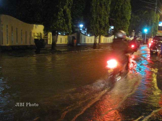 Pengguna jalan melintasi jalan raya yang tergenang air di depan Rumah Dinas Bupati Sukoharjo di kawasan Proliman Sukoharjo, Sabtu (5/1/2013) malam. Banjir juga terjadi di sejumlah wilayah Sukoharjo. (JIBI/SOLOPOS/Trianto Hery Suryono)