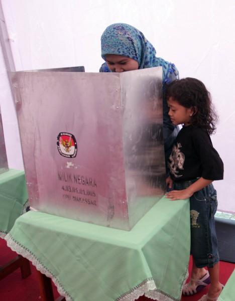 Seorang anak mengintip ibunya yang melakukan pencoblosan di bilik suara pada pemilihan kepala daerah Sulawesi Selatan priode 2013-2018 di TPS 01 Makassar, Selasa (22/1/2013). Pilkada tersebut diikuti tiga calon yakni Syarul Yasin Limpo (incumbent), Ilham Arief Sirajuddin, dan Rudiyanto Asapa yang diikuti 6.283.811 wajib pilih. (JIBI/Bisnis/Paulus Tandi Bone)