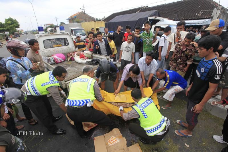 Polisi dibantu warga mengevakuasi jenazah Mulyani, warga Mojosongo, Boyolali  yang menjadi korban kecelakaan di pertigaan Ngemplak, Kartasura, Rabu (20/2/2013). (JIBI/SOLOPOS/Agoes Rudianto)