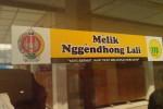 """Stiker kanthi tulisan """"Melik Nggendhong Lali, Yang Berniat Jahat Pasti Melupakan Kebajikan"""" sing ditemplekake ing sawijing kantor ing Kutha Jogja."""