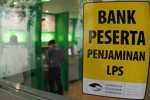 Tanda kepesertaan program penjaminan simpanan dari LPS terlihat di pintu sebuah bank. Sejak LPS beroperasi secara resmi pada 2005 sampai Februari 2013 telah membayarkan klaim simpanan nasabah di 49 bank yang dilikuidasi senilai Rp666 miliar. (koran-jakarta.com)