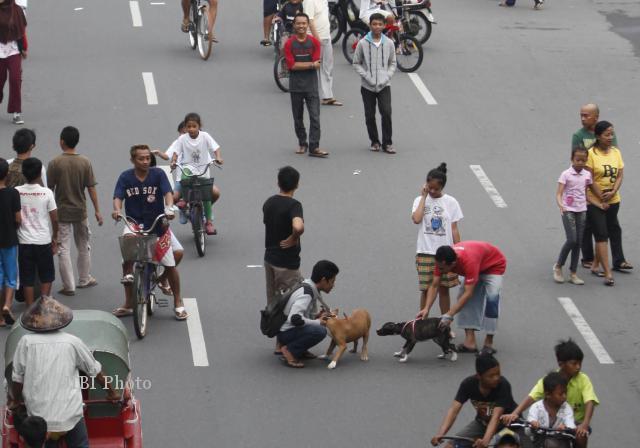 Warga membawa anjing saat menikmati Car Free Day (CFD) di Jl. Slamet Riyadi, Solo, Minggu (14/7)