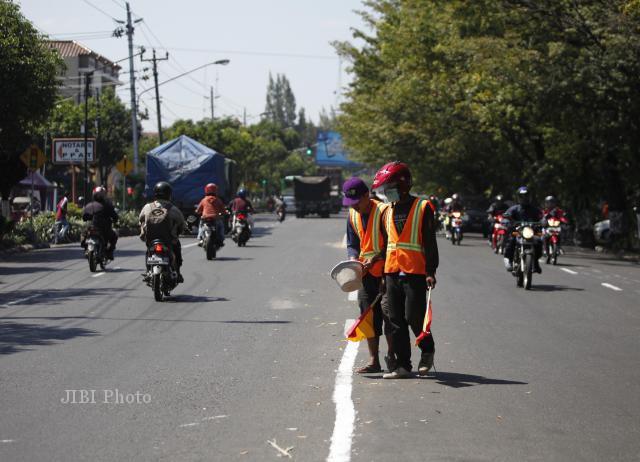 Pekerja membuat garis marka jalan di Jl. Adisucipto, Solo, Rabu (31/7). Pembuatan marka jalan pasca pengaspalan ulang itu dikebut terkait masa mudik Lebaran.
