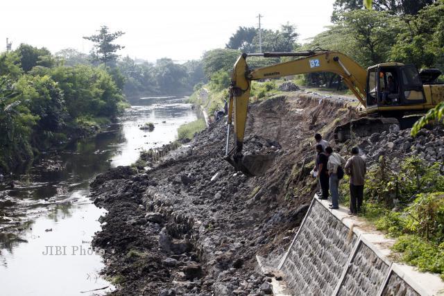 Alat berat digunakan untuk memperbaiki talud Kali Gajah Putih, Solo, Selasa (2/7/2013) yang longsor beberapa waktu lalu. Untuk pengerjaannya, Dinas Pekerjaan Umum (DPU) menggelontorkan anggaran sebesar Rp 800 juta dan memakan waktu hingga empat bulan.