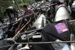 Petugas berusaha menurunkan sepeda motor pemudik asal Solo di halaman kantor Dinas Perhubungan Komunikasi dan Informatika (Dishubkominfo) Solo, Solo, Sabtu (3/8). Sebanyak 318 sepeda motor diangkut dengan 7 truk pada program Mudik Gratis 2013 tersebut.