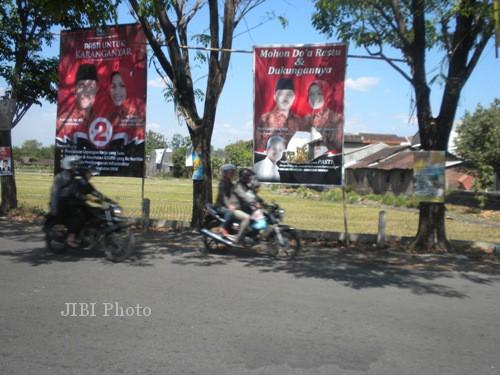 Gambar Pasti (kanan) yang dipasang di sebelah utara Pertigaan Botol, Desa Ngringo, Kecamatan Jaten, Karanganyar, Sabtu (7/9/2013) robek. Sehingga angka 2 yang menjadi nomor urut Pasti tak tampak. (Iskandar/JIBI/Solopos)