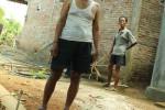 Wardi Utomo berdiri di dekat patok as JJLS yang berada di samping rumahnya.
