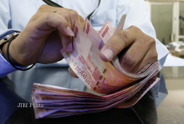 Ilustrasi menghitung uang pecahan Rp100.000 (Dok/JIBI/Bisnis)