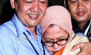 Anggota Komisi II DPR Charun Nisa didekap M, suaminya, saat hendak diwawancarai wartawan seusai diperiksa Komisi Pemberantasan Korupsi (KPK) di Jakarta, Kamis (3/10/2013). (Rahmatullah/JIBI/Bisnis)