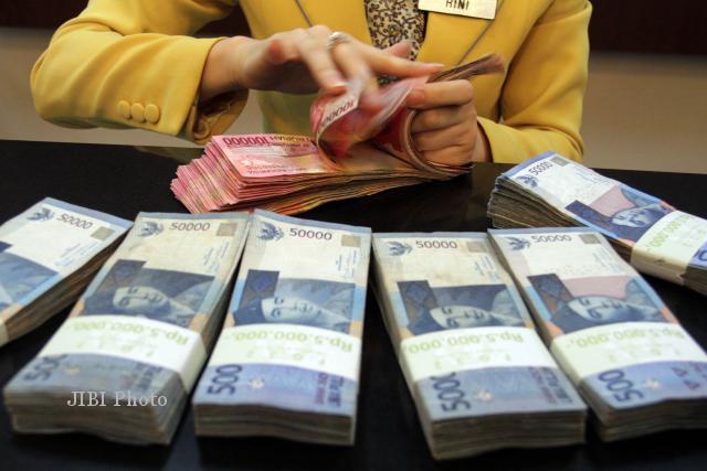 Menghitung Uang Pacahan Rp100.000 (Dok/JIBI/Bisnis)