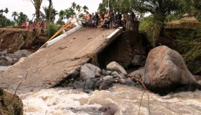 Sejumlah warga berada di ujung jembatan yang ambruk akibat banjir bandang yang melanda Nagari Malampah, Kecamatan Tigo Nagari, Kabupaten Pasaman, Sumatra Barat, Minggu (8/12/2013). Banjir bandang yang menerjang kawasan tersebut Sabtu (7/12/2013) lalu itu mengakibatkan 2 orang warga terbawa arus sungai, 9 unit jembatan rusak, 9 rumah rusak, 6 motor hanyut, dan menimbulkan tanah longsor yang menimbun badan jalan di beberapa titik. (JIBI/Solopos/Antara/Donal Caniago)