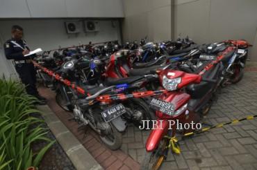 Petugas mendata motor-motor yang disita terkait kasus suap pilkada di halaman parkir Gedung KPK, Jakarta, Selasa (24/12). KPK menyita 31 motor terkait tindak pidana pencucian uang yang menjerat mantan Ketua MK Akil Mochtar. ANTARA FOTO/Rosa Panggabean/Koz/nz/13.