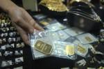 Penjual menunjukkan emas batangan. (Dok/JIBI/Bisnis)