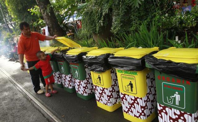 Warga membimbing seorang anak membuang sampah pada tempat sampah yang ...