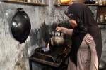 TAK TERPENGARUH HARGA ELPIJI  Wiwin (30) memasak menggunakan kompor gas berbahan bakar biogas limbah tahu di kelurahan Brojolan, Temanggung, Senin (6/1). Sedikitnya 30 keluarga di tempat tersebut tidak terpengaruh dengan kenaikan harga elpiji karena sejak tiga tahun terakhir mereka menggunakan biogas limbah tahu yang murah, aman dan ramah lingkungan. ANTARA FOTO/Anis Efizudin