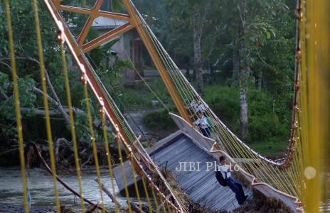 Pelajar SLTP meniti jembatan gantung yang rusak di Sungai Pinjauan, Nagari Pilubang, Padangpariaman, Sumbar, Rabu (8/1). Jembatan gantung yang dibangun pada 2013 itu rusak akibat diterjang luapan sungai sehingga menyebabkan akses dua desa terputus. ANTARA FOTO/Iggoy el Fitra