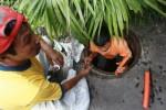 Petugas memotong kabel optik pengganggu saluran air limbah (JIBI/Harian Jogja/Desi Suryanto)