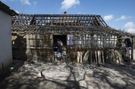 Warga Dusun Laharpang, Suparman menggendong cucunya di depan rumahnya yang rusak terkena dampak letusan Gunung, Kelud, Kediri, Jawa Timur, Jumat (21/2/2014). Setelah status Gunung Kelud dinyatakan siaga, warga yang tinggal di pengungsian kini kembali ke rumahnya meskipun kondisi rumah mereka rusak berat dan hampir tidak bisa ditempati. (JIBI/Solopos/Antara/Rosa Panggabean)