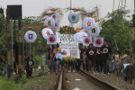 Warga membawa spanduk bergambar partai politik peserta pemilu 2014 di rel kereta api daerah Nusukan Solo, Selasa (25/3). Aksi tersebut mengajak warga di pinggiran rel kereta api untuk datang ke TPS pada 9 April 2014 mendatang.