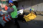 Polisi mengevakuasi mayat Yaya Karyadi warga Pabedilan, Cirebon yang tewas setelah mengalami kecelakaan tunggal di Jl. Ahmad Yani Mendungan, Kartasura, Minggu (9/3/2014). (Burhan AN/JIBI/Solopos)
