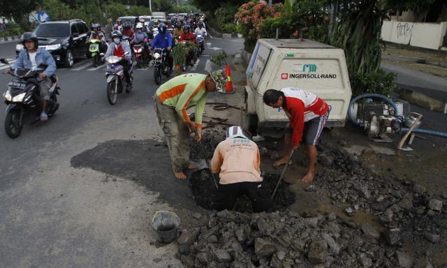 Sejumlah pekerja memperbaiki saluran pipa air Perusahaan Daerah Air Minum (PDAM) Solo di simpang Manahan, Solo, Jawa Tengah, Jumat (25/4/2014). Perbaikan tersebut dilakukan karena terdapat kebocoran yang mengakibatkan genangan air yang mengganggu warga. (Ardiansyah Indra Kumala/JIBI/Solopos)