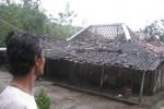 Seorang warga melihat kondisi genteng rumah milik Suto, warga Dusun Sepangan Jetis, Desa Sendangijo, Kecamatan Selogiri, Wonogiri disapu angin ribut, Sabtu (12/4/2014). (Trianto HS/JIBI/Solopos)