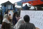Pemilih melihat daftar calon tetap (DCT) yang ditempel di papan pengumuman TPS XI, Kaloran, Kelurahan Giritirto, Wonogiri sebelum menggunakan hak pilihnya, Rabu (9/4/2014).(JIBI/Solopos/Trianto Hery Suryono)