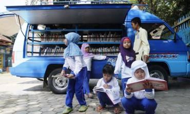 Peserta didik di Pra Taman Kanak-Kanak dan Taman Kanak-Kanak Lazuardi Kamila membaca buku yang disediakan perpustakaan keliling yang beroperasi di wilayah Kecamatan Banjarsari, Solo, Jawa Tengah, Jumat (16/5/2014). Aksi yang dilabeli tajuk 1.000 Mata Membaca tersebut dilaksanakan untuk menumbuhkan minat baca anak sekaligus memperingati Hari Buku Nasional yang jatuh Sabtu (17/5/2014). (Ardiansyah Indra Kumala/JIBI/Solopos)