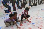 Sejumlah bocah menempelkan cap telapak tangan mereka di kain saat peringatan Hari Tanpa Tembakau Sedunia di arena Car Free Day (CFD) Kota Solo, Jl Slamet Riyadi, Solo, Jawa Tengah, Minggu (25/5/2014). Aksi tersebut sejatinya digelar demi mengajak warga menjauhi rokok yang diyakini sebagian kalangan bisa berakibat fatal bagi kesehatan. (Septian Ade Mahendra/JIBI/Solopos)