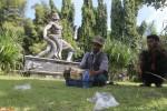Pengunjung berteduh di bawah pohon Taman Banjarsari, Solo, Jawa Tengah, Selasa (27/5/2014). Patung Bima bertarung dengan naga yang menghiasi taman kota tersebut kondisinya rusak sejak 2012 dan hingga kini belum diperbaiki. Tangan kiri Bima yang memegang bagian kepala ular naga buntung, sedangkan sampah plastik berserakan, tak enak dipandang. (Septian Ade Mahendra/JIBI/Solopos)