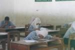 Seorang siswi salah satu SLTP di Wonogiri tidur di ruang kelas usai mengerjakan soal ujian nasional, Rabu (7/5/2014). (Trianto HS/JIBI/Solopos)