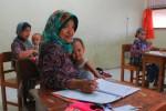Peserta kejar Paket B menggendong anaknya yang masih balita sambil mengerjakan ujian di salah satu ruang di SMP Muhammadiyah 1 Klaten, Selasa (6/5/2014). (Shoqib Angriawan/JIBI/Solopos)