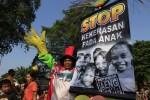 Pengunjung membawa poster saat melakukan aksi anti kekerasan anak di car free day (CFD) Jl. Slamet Riyadi, Solo, Minggu (11/5/2014). Aksi tersebut juga menghimbau orang tua agar memperhatikan keselamatan anak. (JIBI/Solopos/Septian Ade Mahendra)