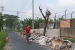 Salah seorang warga melintas di samping tempat pembuangan sampah (TPS) yang berlokasi di Dukuh Nungso, Desa Manang, Kecamatan Grogol, Jumat (9/5/2014). Sebagian sampah terlihat meluber ke samping lokasi TPS. (JIBI/Solopos/Ivan Andimuhtarom)