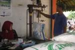 Salah seorang pegawai kios beras di Pasar Wates sedang menimbang beras, Selasa (24/6/2014). (Holy Kartika N.S/JIBI/Harian Jogja)
