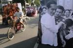 Pengendara sepeda melintas di deretan foto-foto yang bertemakan Joko Widodo alias Jokowi, mantan wali kota Solo yang kini dicalonkan poros politik besutan PDI Perjuangan sebagai presiden dalam Pemilihan Umum Presiden dan Wakil Presiden (Pilpres) 2014. Foto-foto itu dipajang di kawasan Ngarsopuro, Solo, Jawa Tengah, Minggu (29/6/2014). (Septian Ade Mahendra/JIBI/Solopos)