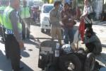 Anggota satlantas Polres Wonogiri mengawasi pengendara sepeda motor jenis vespa berpenumpang tiga yang ditilang di Jalan Pemuda Wonogiri, Jumat (30/5/2014). (Trianto HS/JIBI/Solopos)