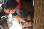 Pemilik bengkel, Erwin BS, 27, warga Lingkungan Salak, Kelurahan Giripurwo, Wonogiri (kanan, bawag) bersama rekannya melihat bekas congkelan di pintu masuk ruang bengkel, Minggu (1/6/2014). (JIBI/Solopos/Trianto HS)