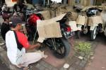 Pekerja mengepak sepeda motor yang akan dipaketkan ke sejumlah daerah di Jawa Tengah, dan Jawa Timur di Stasiun Senen, Jakarta, Minggu (13/7/2014). Pengiriman kendaraan roda dua melalui perusahaan jasa ekspedisi pada bulan Ramadan 2014 menjelang Lebaran 2014 meningkat hingga 50%. (Dedi Gunawan/JIBI/Bisnis)