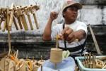 Penjual mainan tradisional, Edi, memainkan gasing dari bambu untuk menarik pembeli di Baluwarti, Pasar Kliwon, Solo, Jawa Tengah, Kamis (3/7/2014). Mainan tradisional berupa gasing dan ethek-ethek bikinan warga Gunung Kidul tersebut dijual dengan harga Rp7.000 hingga Rp10.000 per biji. (Septian Ade Mahendra/JIBI/Solopos)