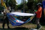 Petugas Satpol PP Boyolali menurunkan spanduk kedaluwarsa yang terpasang di Jl. Pandanaran, Senin (11/8/2014). (JIBI/Solopos/Septhia Ryanthie)