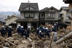 Police officers search for survivors at a site where a landslide swept through a residential area at Asaminami ward in Hiroshima